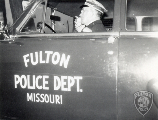 Fulton City Marshal Tom Edson sits in a patrol car.